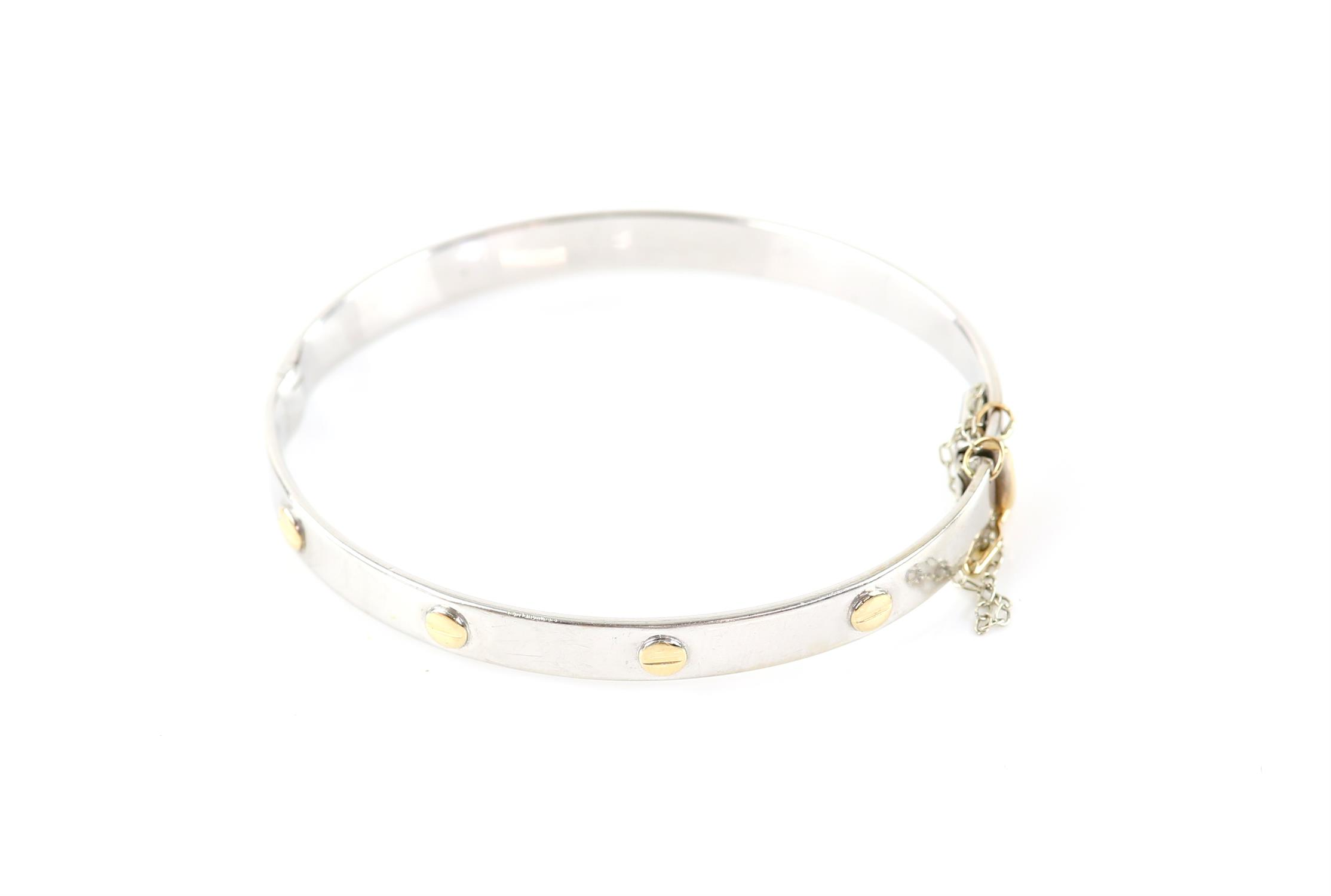 Bi-colour gold hinged bangle, white gold 6.5mm band, with yellow metal screw detail,