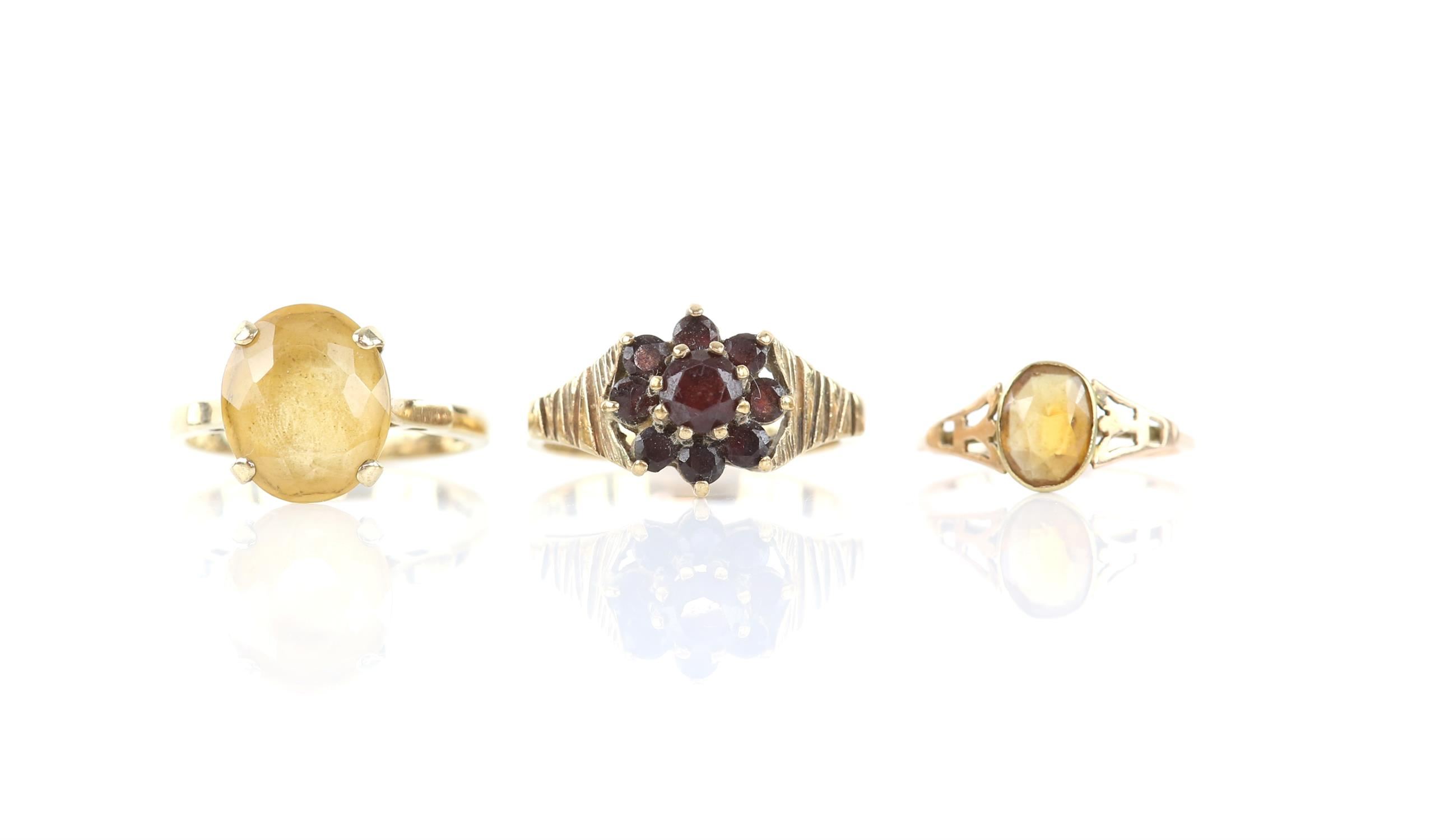 Three gem set rings, including a garnet cluster ring, size P 1/2, and two single stone citrine
