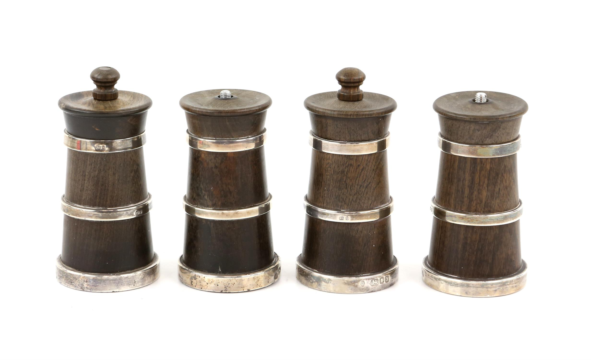 Four very similar walnut and silver mounted pepper grinders (two top screws although present
