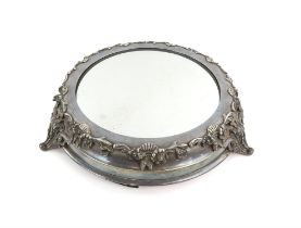 Silver plated mirrored cake stand with moulded shell and scroll decoration on three shaped feet,