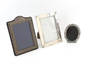 Three silver photo frames of varied designs and dates