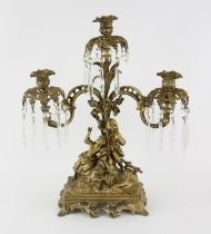 Early 20th century gilt metal figural three light candelabra with scroll arms, a young man and