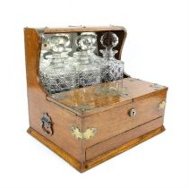 Oak and brass three bottle tantalus with hinged lid revealing fitted interior with mirrored back.