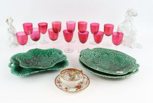 Fourteen cranberry drinking glasses, two Rosenthal figures, four green leaf moulded plates and a