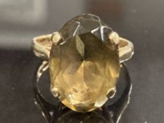 9CT YELLOW GOLD SMOKEY QUARTZ RING COMPRISING OF A SINGLE LARGE OVAL STONE IN A FOUR CLAW SETTING