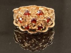 A 9CT YELLOW GOLD SEVEN STONE GARNET RING SET IN AN ORNATE SETTING SIZE K 1/2 4.8G GROSS