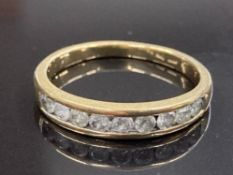 18CT YELLOW GOLD AND DIAMOND HALF ETERNITY RING COMPRISING OF NINE ROUND BRILLIANT CUT DIAMONDS IN A