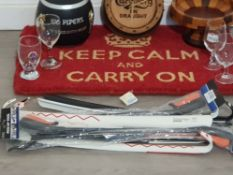 A keep calm and carry on door mat along with a 100 pipers scotch whiskey ice bucket carlsberg wall