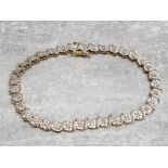 A 10k yellow gold and diamond tennis bracelet comprising of 35 .02 carat diamonds in illusion