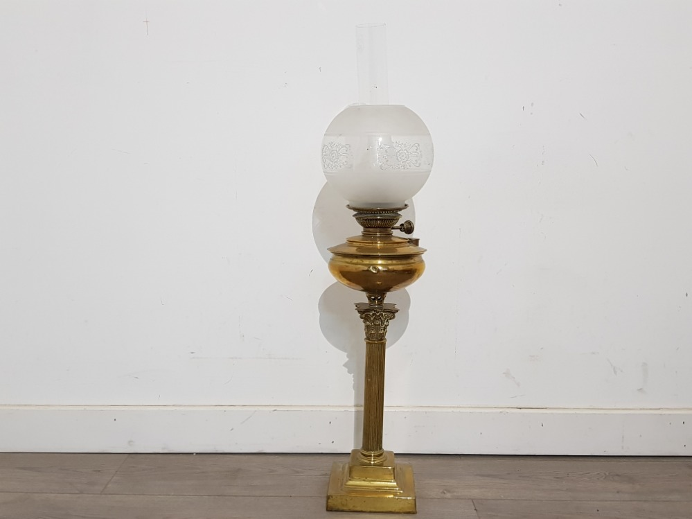 A Victorian brass oil lamp with glass shade, supported on corinthian column 53cm high excluding