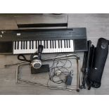 A Yamaha PSR-60 keyboard on stand, Dynatron dual unit stereo headphones, a pedal and music stands.