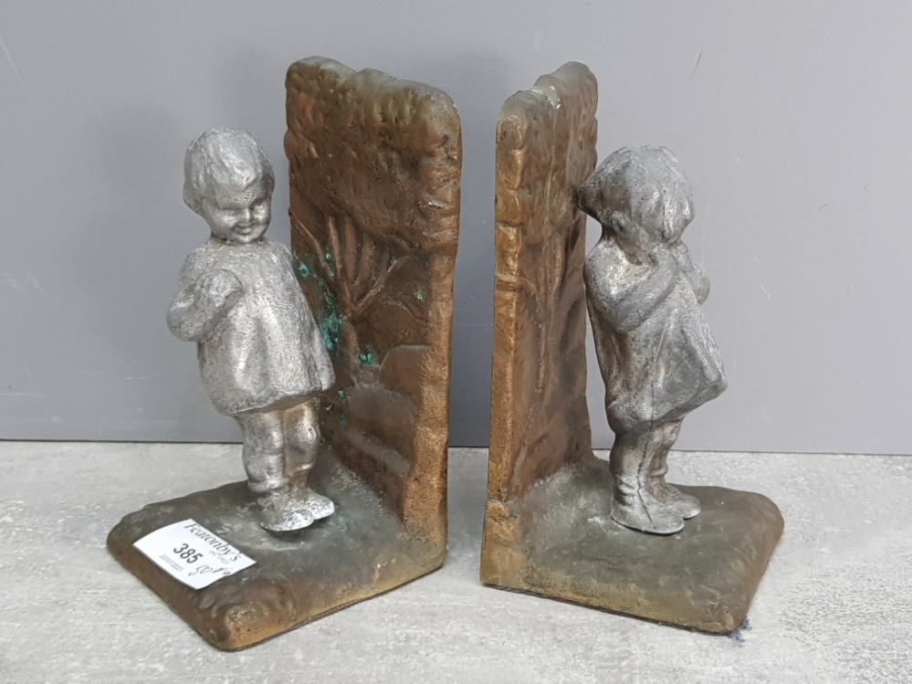 A pair of cast iron and aluminium bookends in the form of two little girls 15cm high.