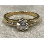 Ladies 9ct gold CZ ring. Featuring a round centre stone set with 3 CZs on each shoulder. Size P 2.