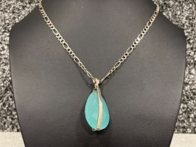Ladies Silver Figaro chain with blue pear shaped stone pendant