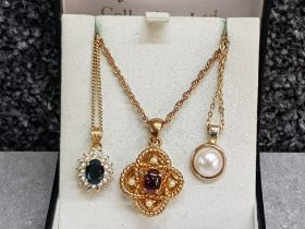 Three gold plated pendants one set with a garnet, and chains.