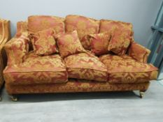 A three seater sofa upholstered in floral patterned material.