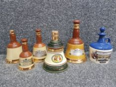 Five Bells scotch whisky decanters and a Lamb's 100 navy rum decanter, all empty.