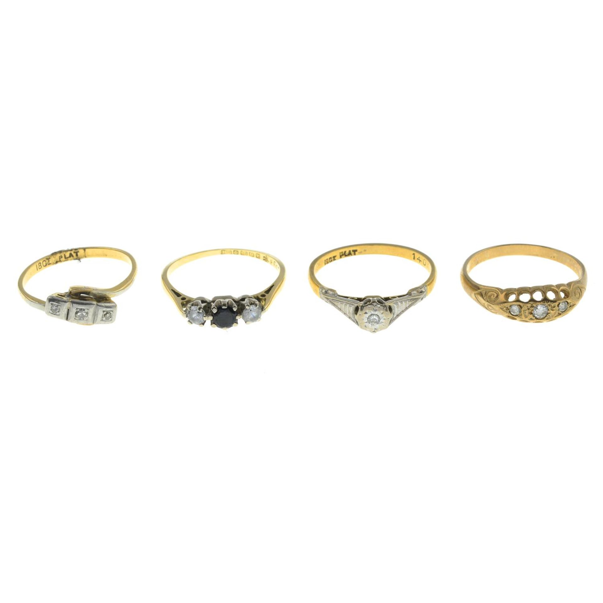 Four gem-set rings.18ct gold cubic zirconia and black gem three-stone ring,
