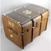 An old brown canvas and wooden bound travel trunk with applied Hogwarts crest to top and H.P