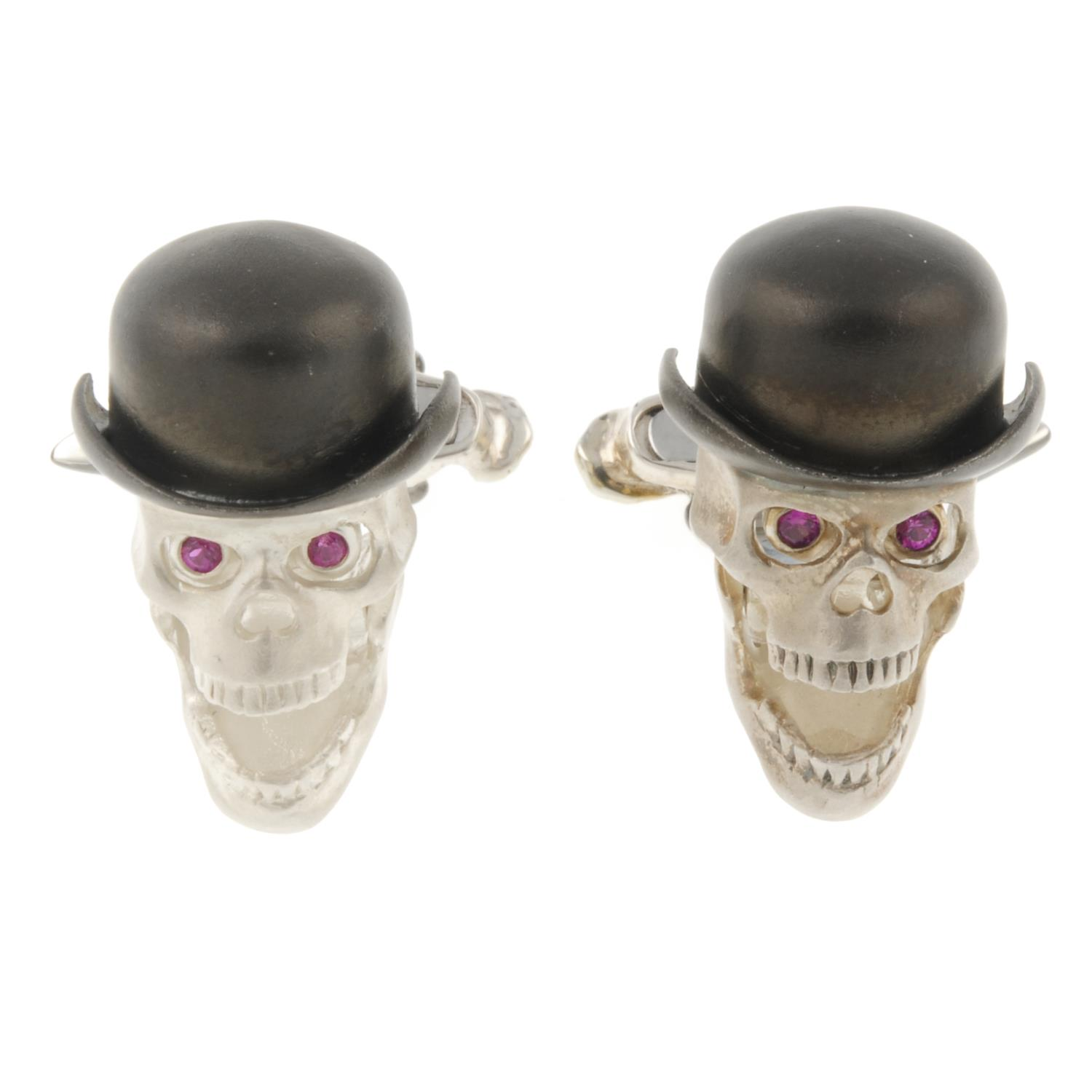 A pair of silver skull cufflinks, with articulated jaw and ruby eyes, by Deakin and Francis.