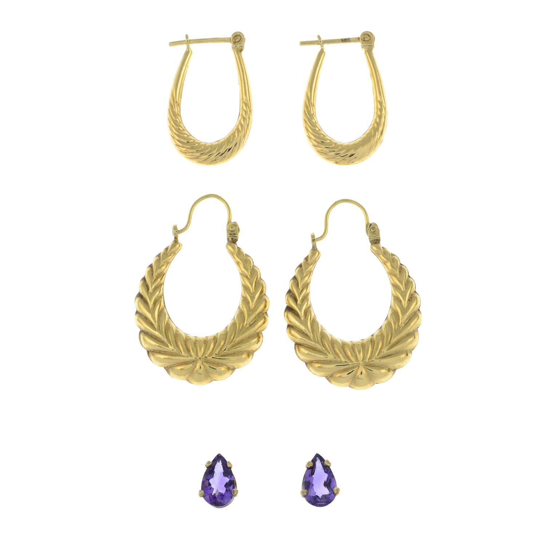 A pair of amethyst stud earrings and two pairs of hoops.Stud earrings stamped 10K.