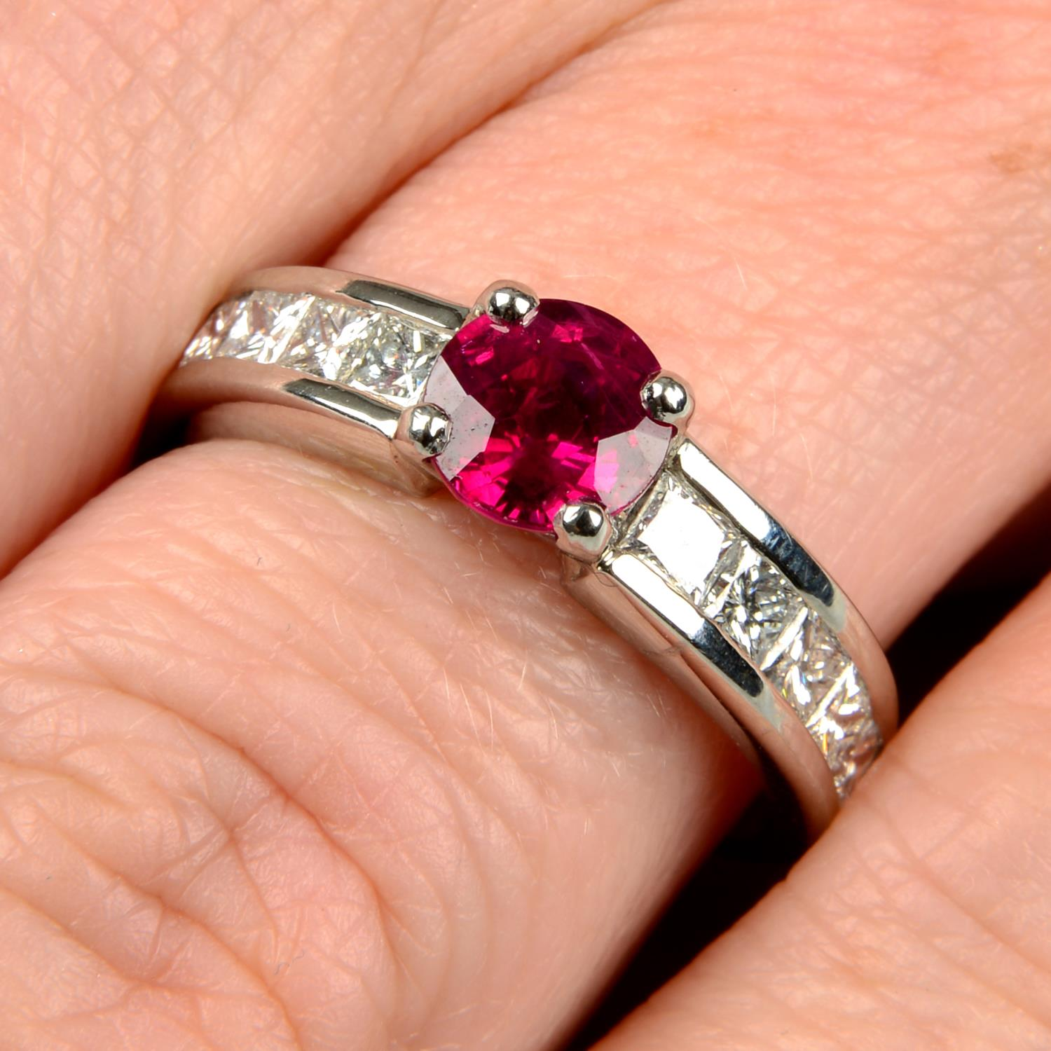 A platinum ruby single-stone ring, with square-shape diamond line shoulders.