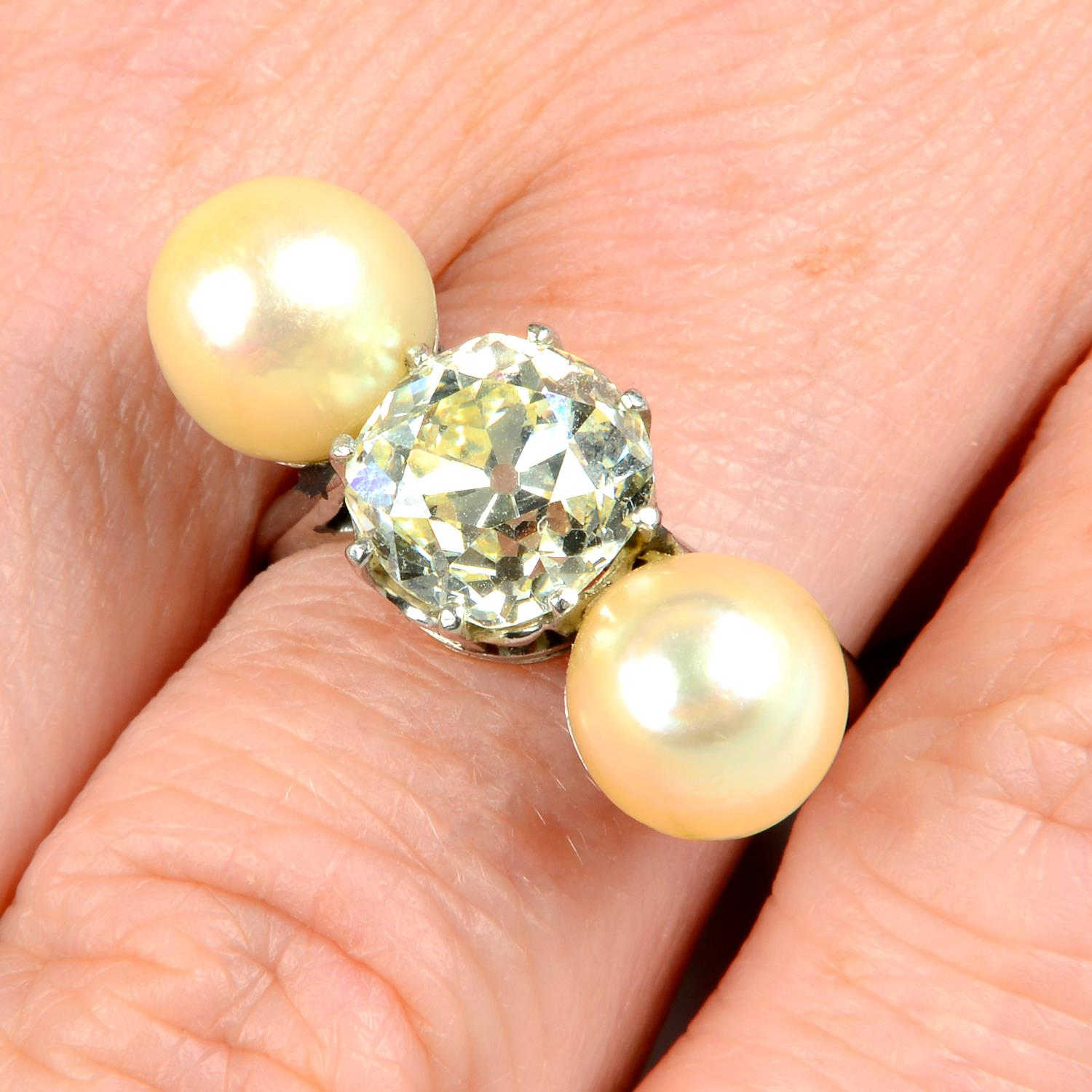 A mid 20th century platinum old-cut diamond and pearl three-stone ring.