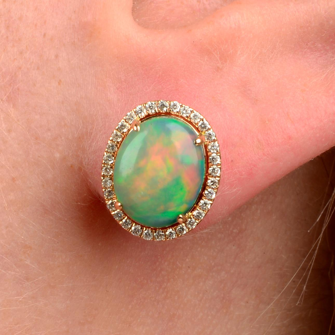 A pair of opal cabochon and brilliant-cut diamond cluster earrings.Total opal weight 2.85cts.Total