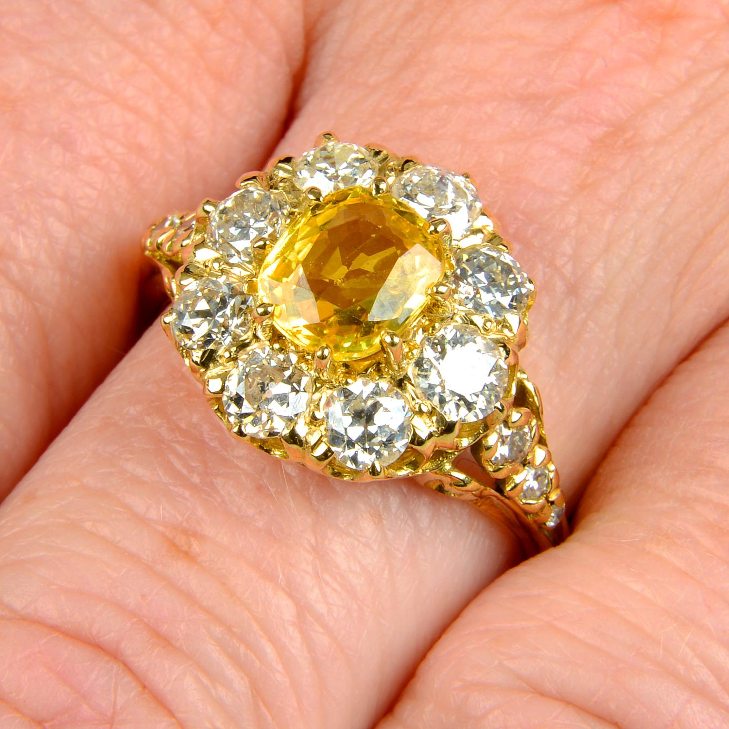 A yellow sapphire and old-cut diamond cluster ring.Sapphire calculated weight 1.05cts,