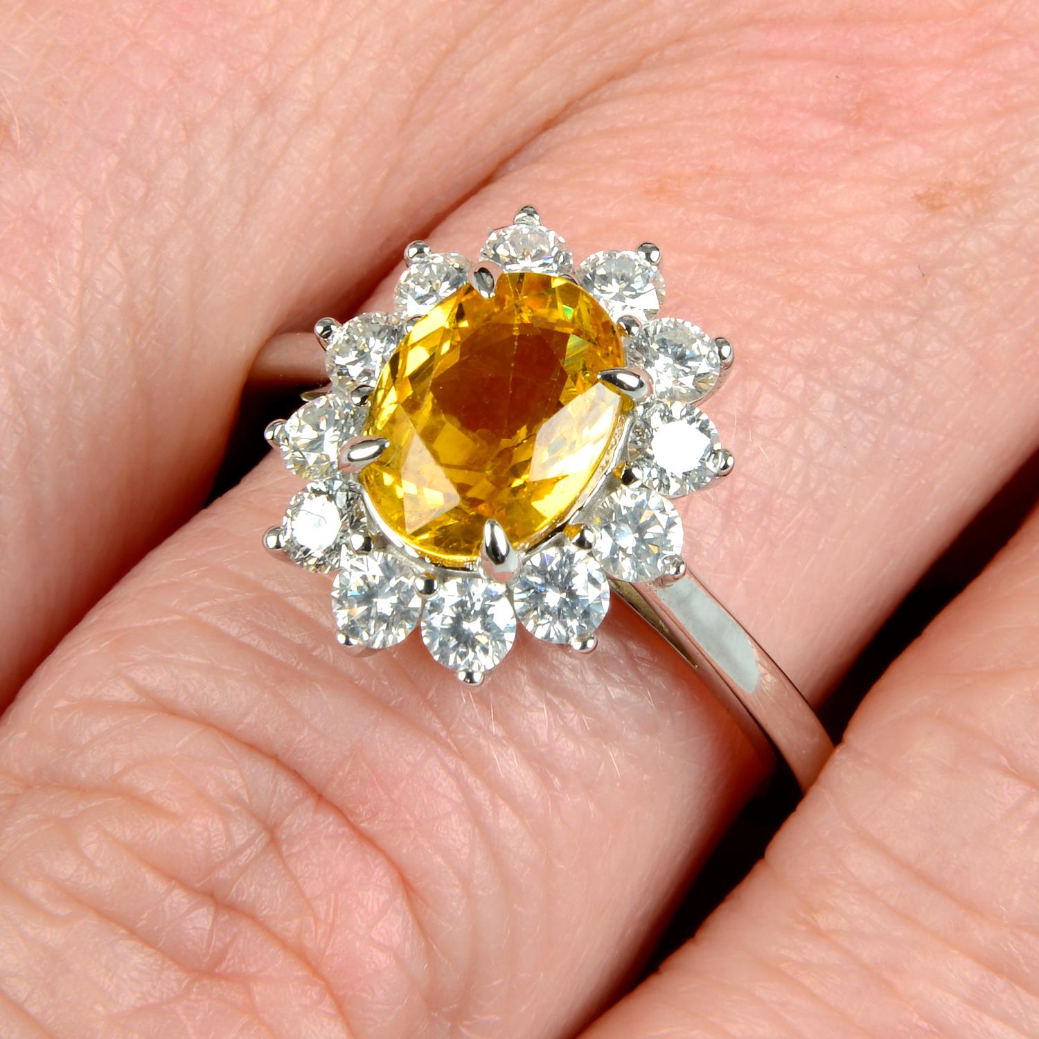 A yellow sapphire and brilliant-cut diamond cluster ring.Sapphire calculated weight 1.73cts,