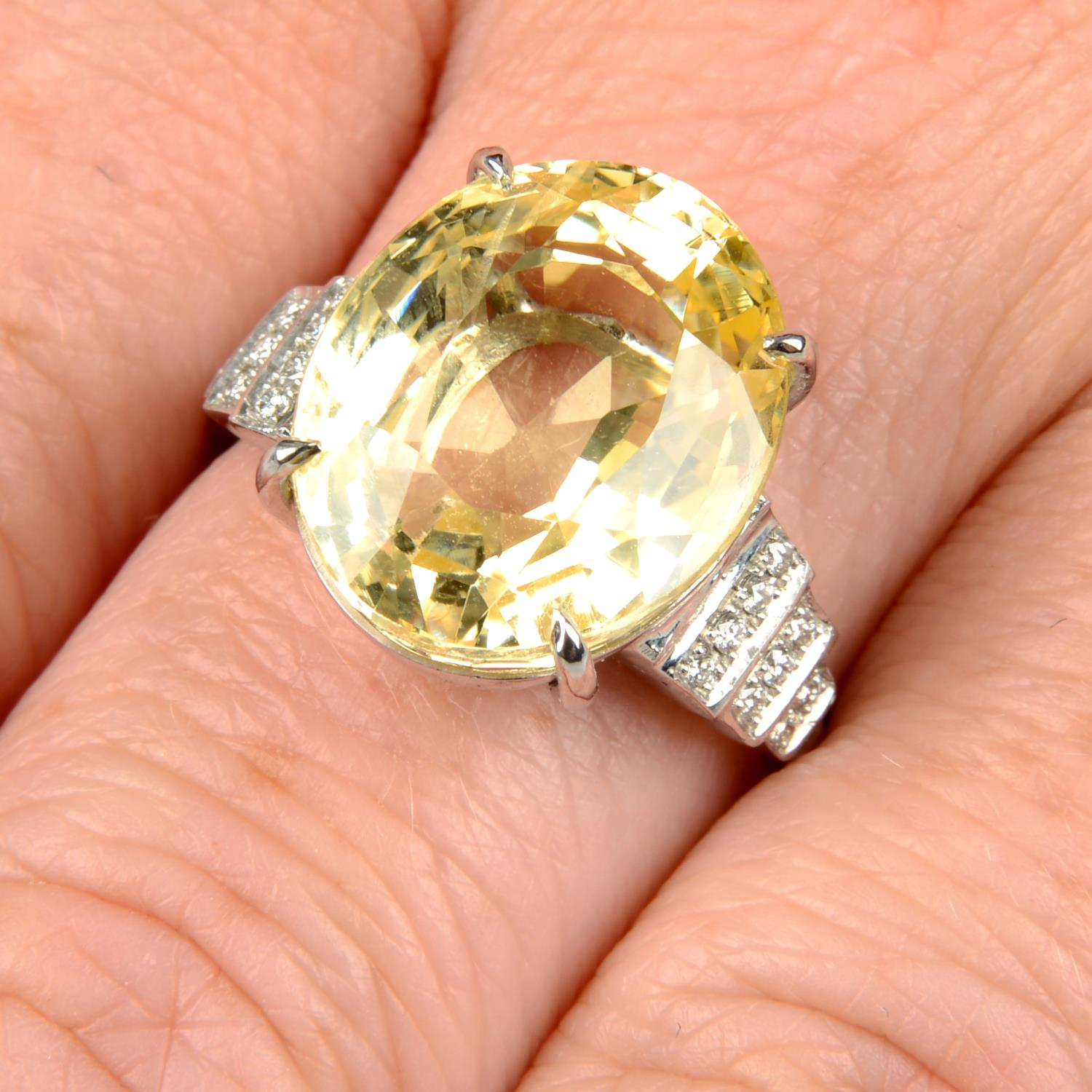 A yellow sapphire and diamond ring.Sapphire weight 15.31cts.Estimated total diamond weight 0.10ct,