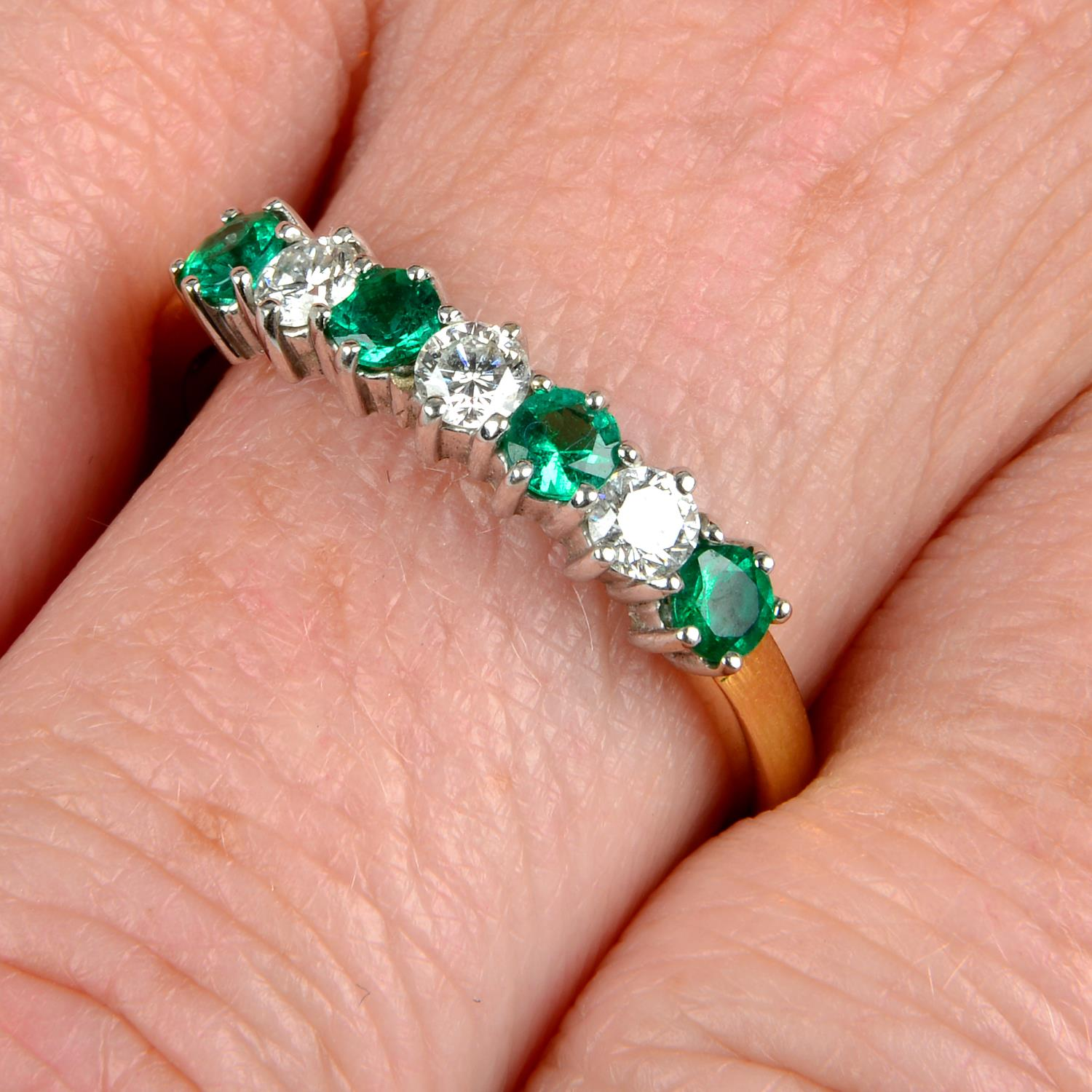 An 18ct gold alternating emerald and brilliant-cut diamond half eternity ring.Estimated total