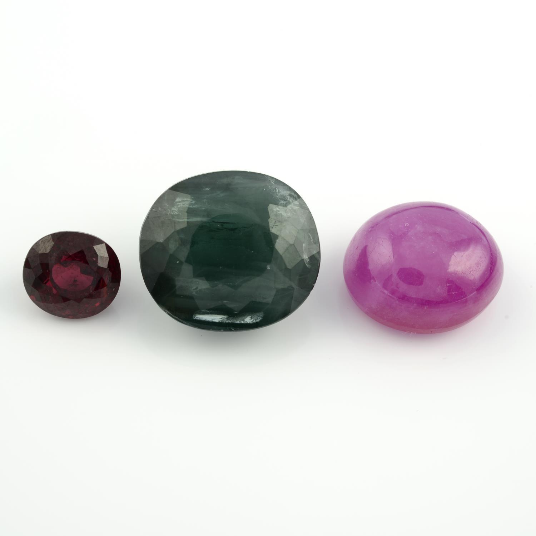An oval shape rhodolite garnet, an oval shape ruby cabochon and an oval shape apatite.