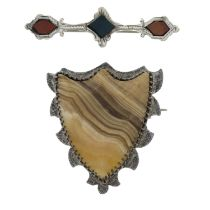 Three Scottish agate brooches and an Irish serpentine brooch and a silver olive fork.Three with