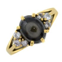 A synthetic star sapphire and diamond ring.Estimated total diamond weight 0.24ct.Stamped 750.Ring