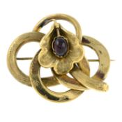 A late 19th century gold floral brooch, with garnet highlight.Length 4.5cms.
