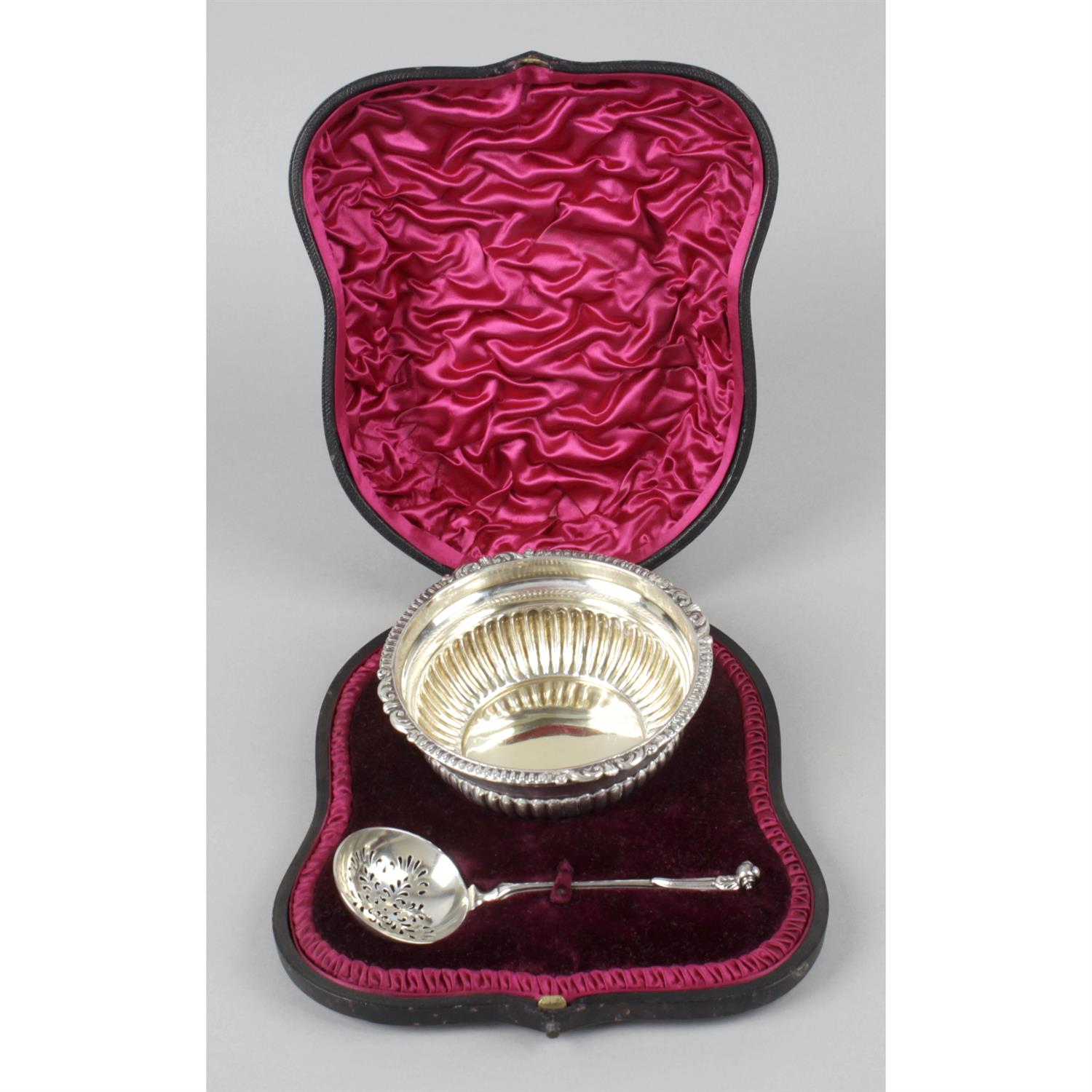 A late Victorian silver sugar bowl and sifter spoon, in fitted case.