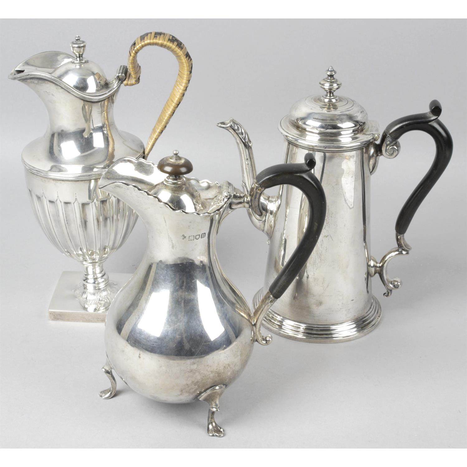 An Edwardian silver coffee pot, together with a late Victorian lidded jug and a further lidded jug.