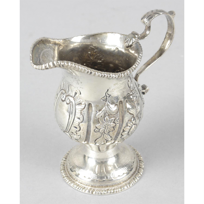 An Edwardian silver floral embossed pedestal cream jug.