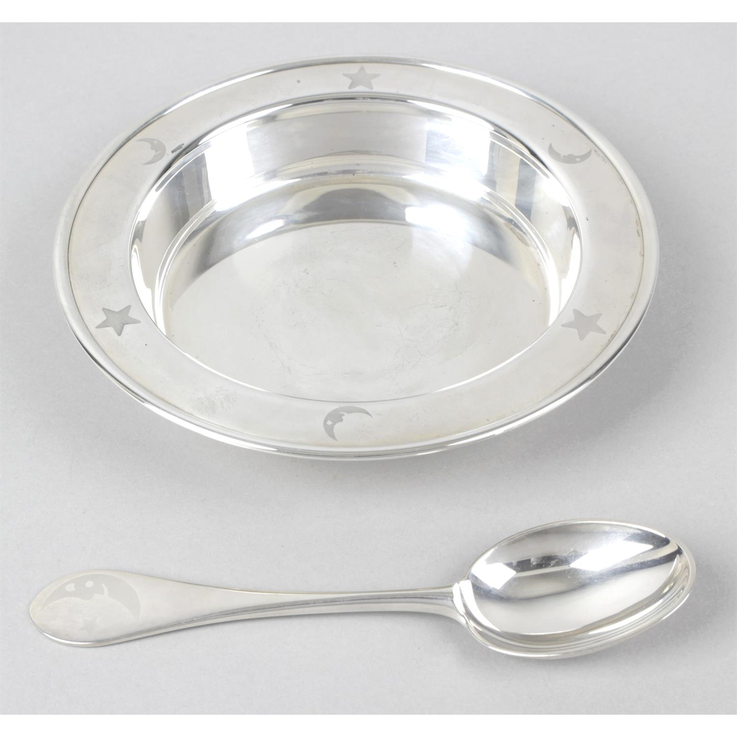 A modern silver child's dish and spoon.