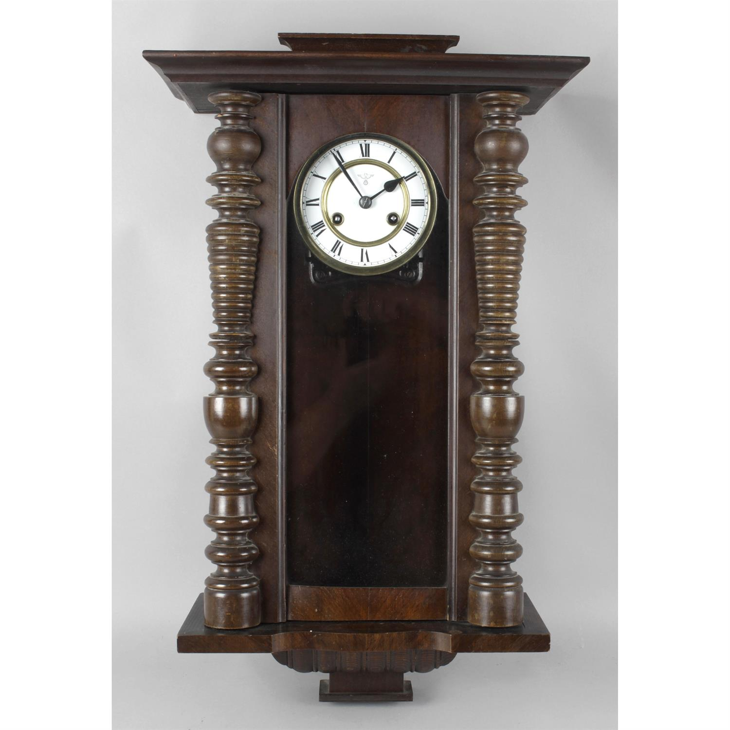 A stained wooden cased Vienna style wall clock