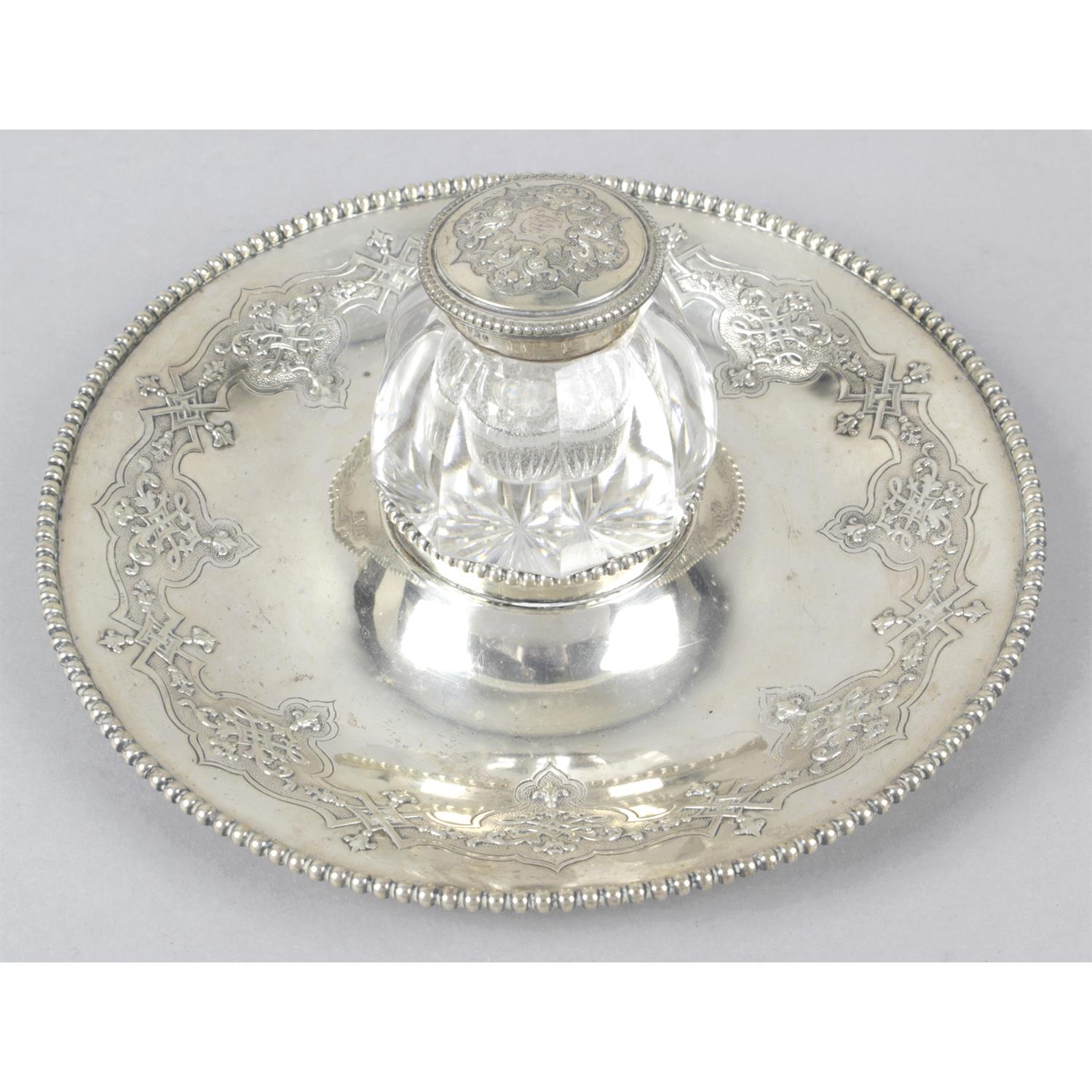 A Victorian silver inkstand with central glass ink pot.