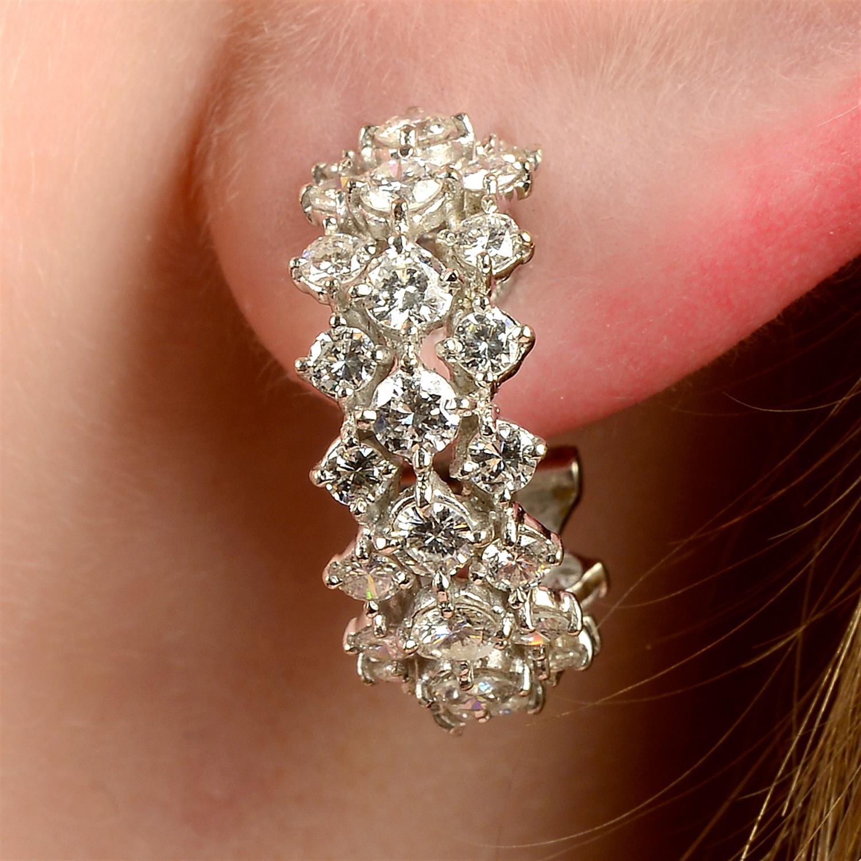 A pair of 18ct gold diamond half hoop earrings.