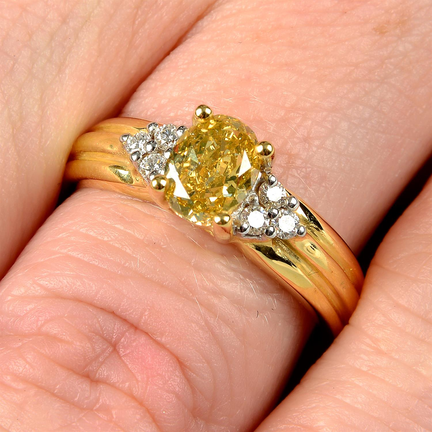 An 18ct gold oval-shape 'brownish-yellow' diamond ring, with brilliant-cut diamond trefoil sides.