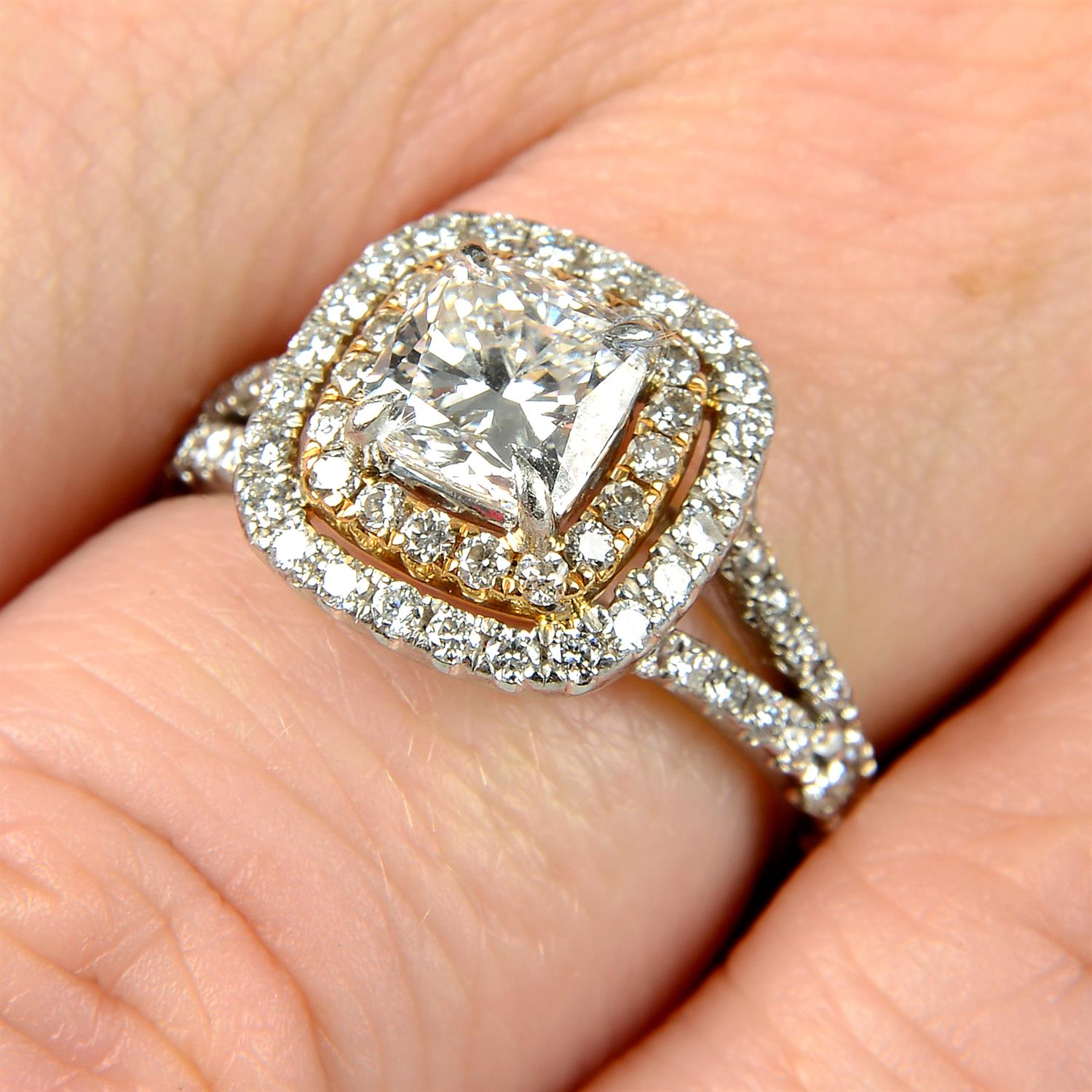 A platinum cushion-shape diamond ring, with brilliant-cut diamond surrounds and shoulders.