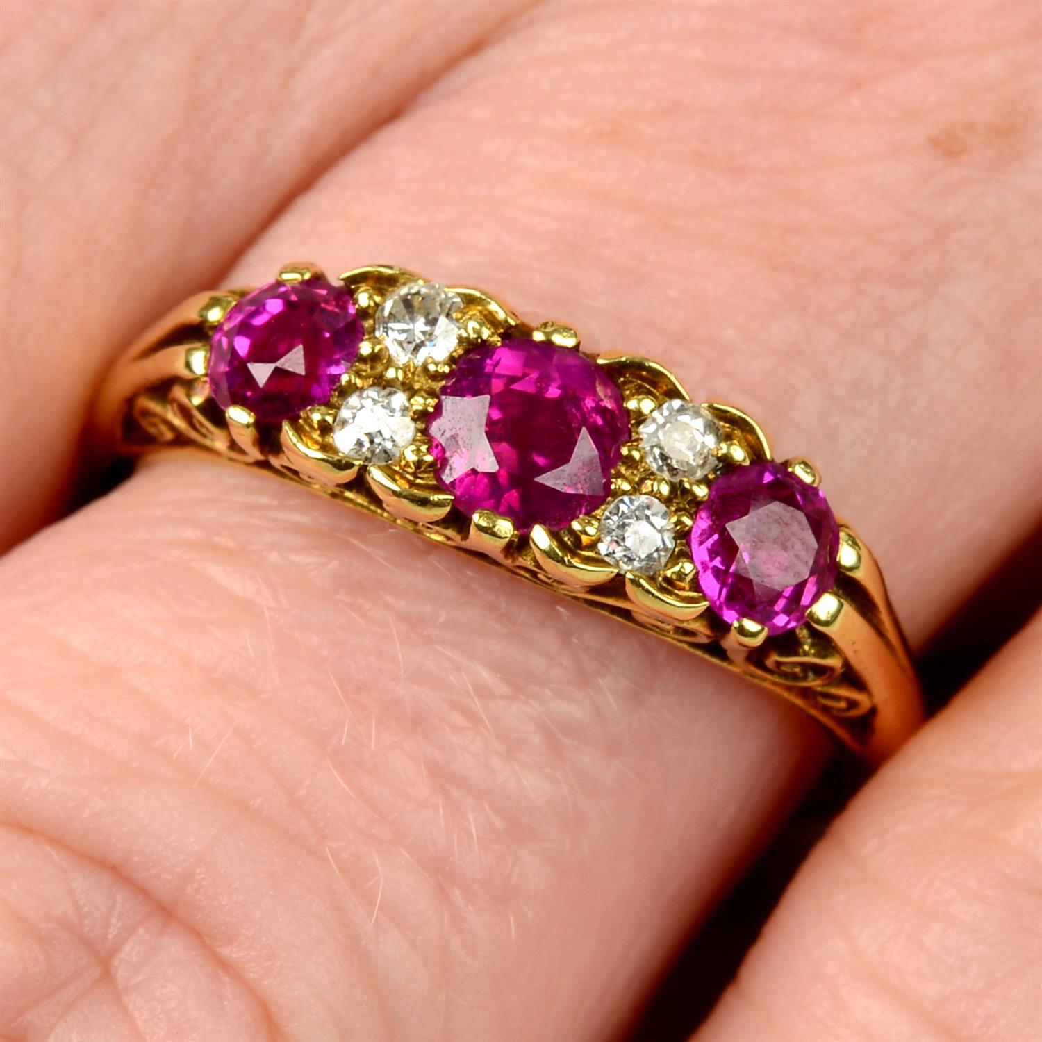 An 18ct gold slightly graduated ruby three-stone ring, with diamond double spacers and scrolling