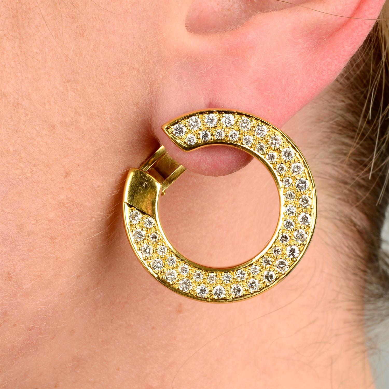 A pair of pavé-set diamond circular earrings.