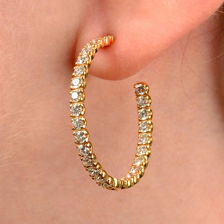 A pair of brilliant-cut diamond hoop earrings.