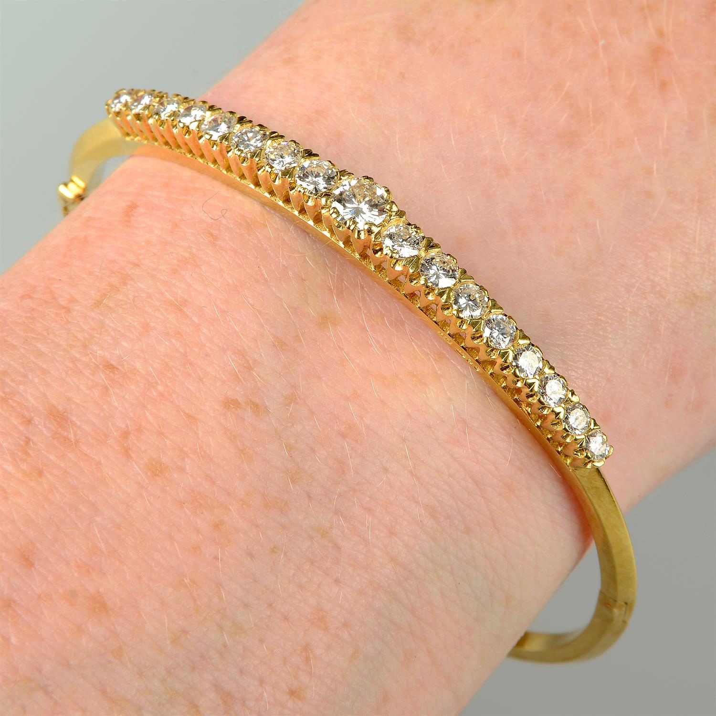 A graduated brilliant-cut diamond hinged bangle.
