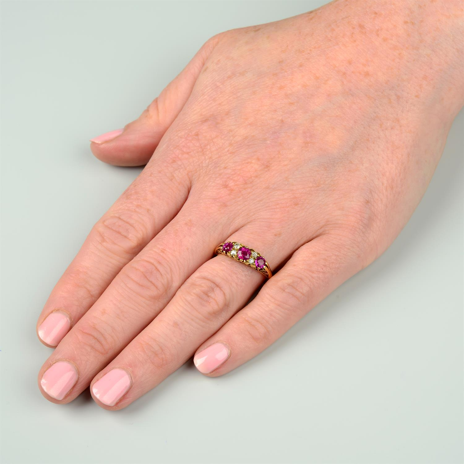 An 18ct gold slightly graduated ruby three-stone ring, with diamond double spacers and scrolling - Image 6 of 6